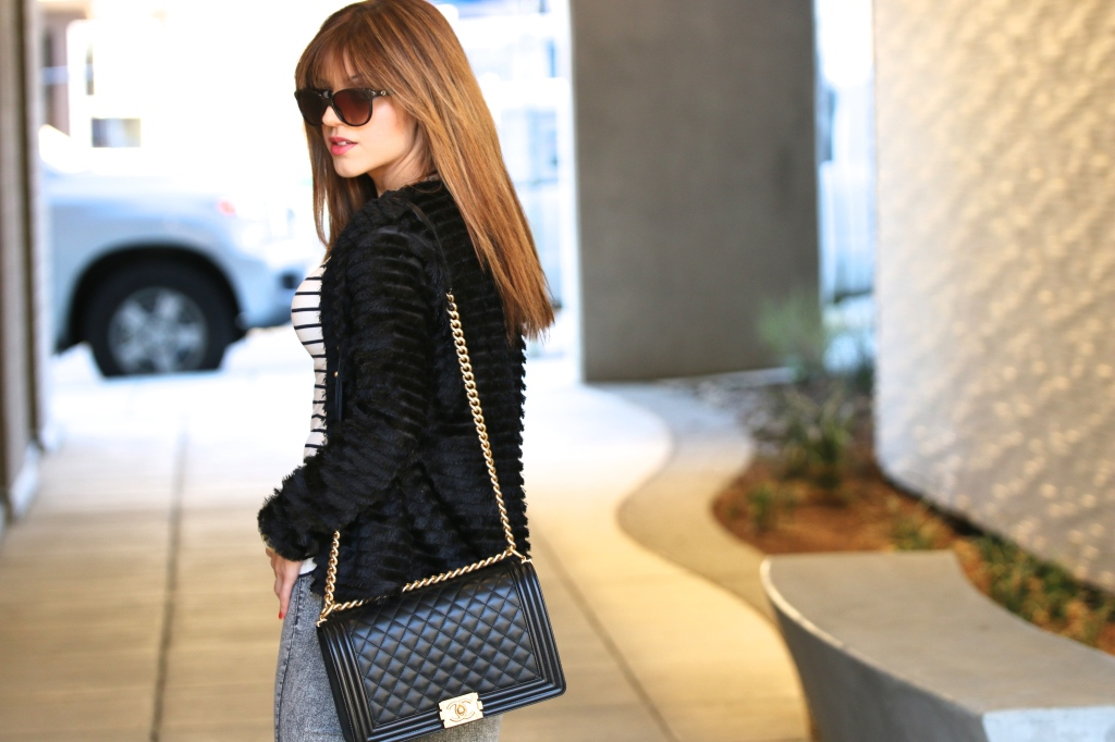 H&M Black Fringe Jacket, Chanel Le Boy Bag Black and Gold, High-waisted grey Jeans, Striped Top, Gucci Sunglasses